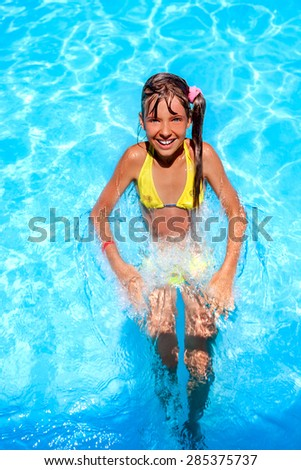 Little girl swimming on  mattress in blue water.