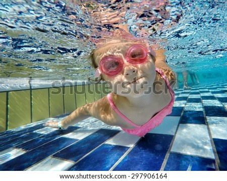 little girl swimming underwater and smiling - stock photo
