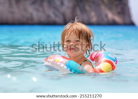 Little girl swims in the sea alone. - stock photo