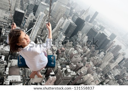Little girl swinging with the city in the background