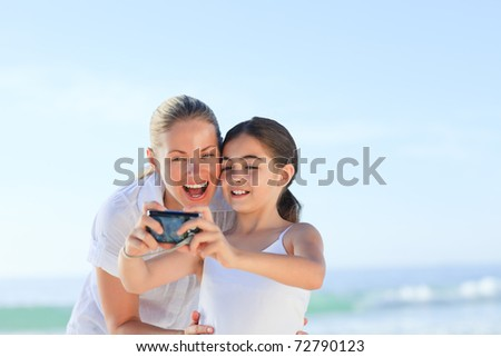 Little girl taking a photo of herself and her mother - stock photo