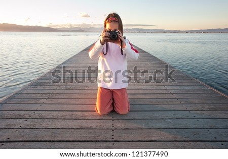 little girl taking a photograph on a pier