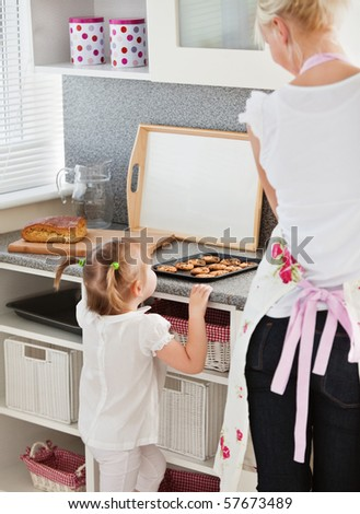 Little girl taking a small cookie in the kitchen - stock photo