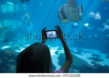 little girl taking picture of fish at aquarium on camera phone - stock photo