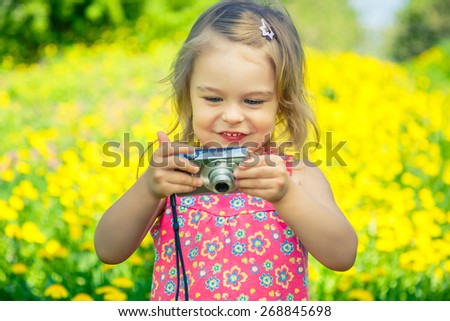 Little girl taking pictures with point and shoot camera - stock photo