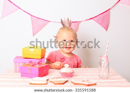 little girl taking presents at first birthday party - stock photo
