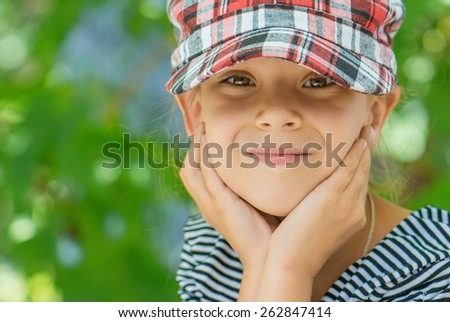 Little girl talking in plaid cap against green of the Park in summer. - stock photo