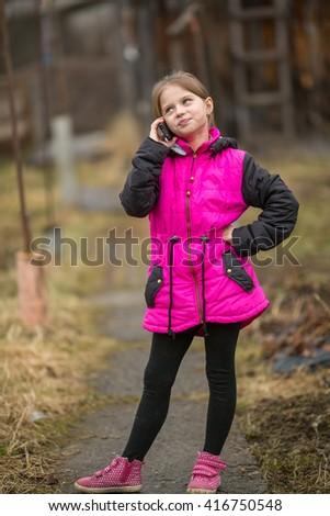 Little girl talking on mobile phone outdoors. - stock photo
