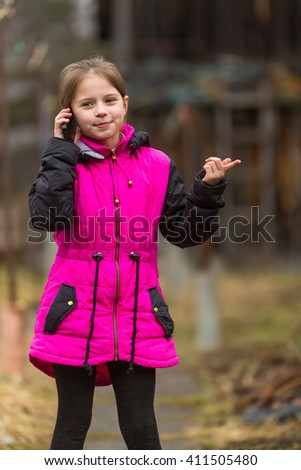 Little girl talking on phone standing in the yard. - stock photo