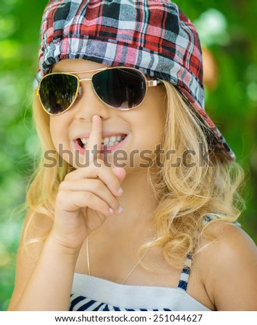 Little girl talking presses finger to his lips against green of Park in summer.