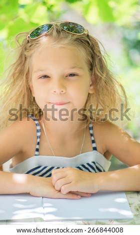 Little girl talking Silit at table and wrote against green of Park in summer. - stock photo