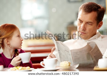Little girl talking to her father absorbed in newspaper