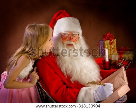 Little Girl Talking to Santa Clause While He Writes Magic Feather in the Book - stock photo