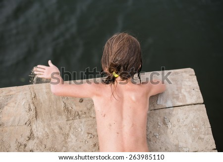 Little girl tanning and playing with sand on wooden deck at the lake on hot summer day. Having fun during vacation. - stock photo
