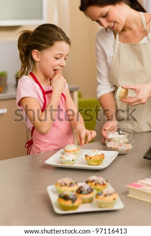 little girl taste sprinkles decorating cupcakes with mother at home