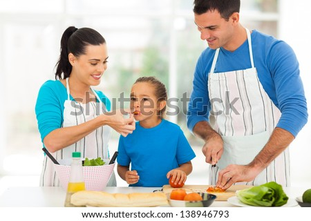 little girl tasting tomato while her parents cooking in kitchen at home