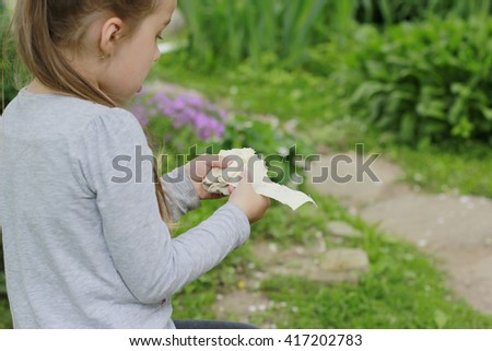 Little girl tearing into pieces an unleavened wheat cake (lavash) in hands