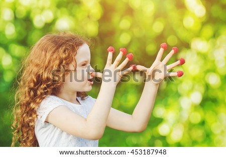 Little girl teasing is putting fingers to nose with raspberry. - stock photo
