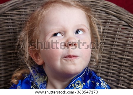 Little girl thinking hard in studio portrait. Funny and natural expression. - stock photo