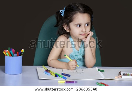 Little girl thinking while drawing - stock photo