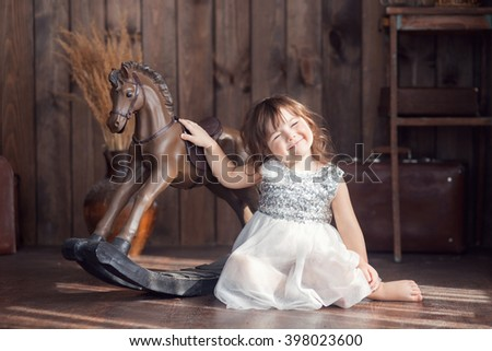little girl three years sitting on the floor next to a rocking horse, a beautiful light, the sun, eyes closed, smiling - stock photo