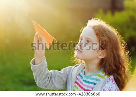 Little girl throwing paper airplane in  sunset light. Happy childhood, travel, vacation concept. - stock photo