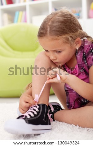 Little girl ties shoes with great care and concentration - stock photo