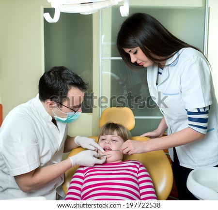 little girl to the dentist in the dental chair sits next to a doctor to do the dentist to see if his teeth were okay/ little girl at the dentist