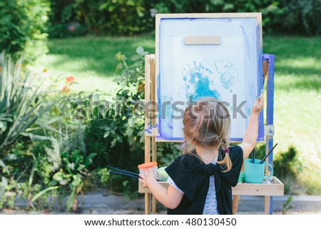 Little girl toddler painting with her hands outdoors in the garden