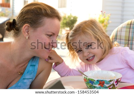 Little girl toddler touching her mothers shoulder softly while mother looks at her daughter at the table - stock photo