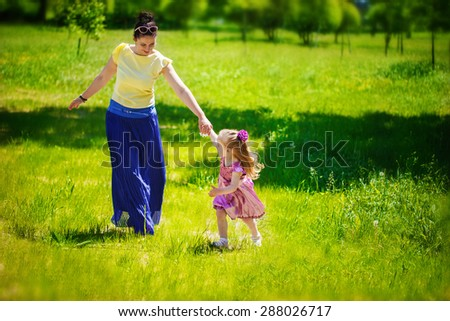 Little girl together with mother run and play on a grass in the sunny summer day.