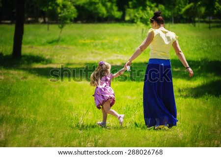 Little girl together with mother run and play on a grass in the sunny summer day. Back view.