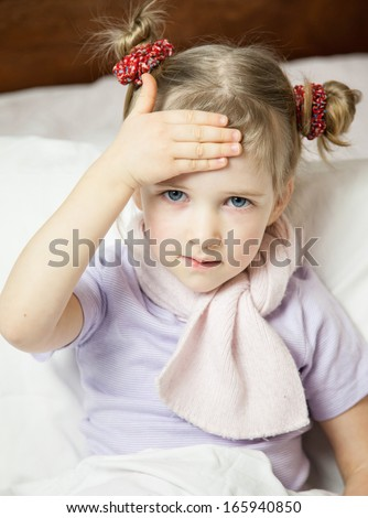 Little girl touching her forehead - closeup portrait - stock photo