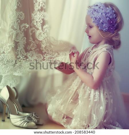 Little girl touching wedding dress - stock photo