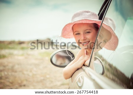 little girl traveling by car at sea - stock photo