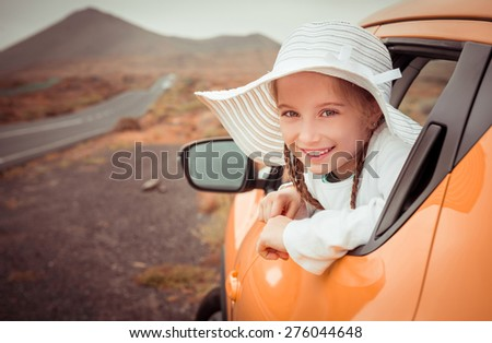 little girl traveling by car in the mountains - stock photo