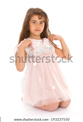 little girl tries on a dress on a white background
