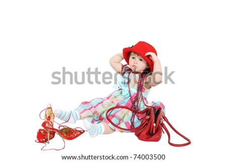 little girl tries on a mum's hat and a beads
