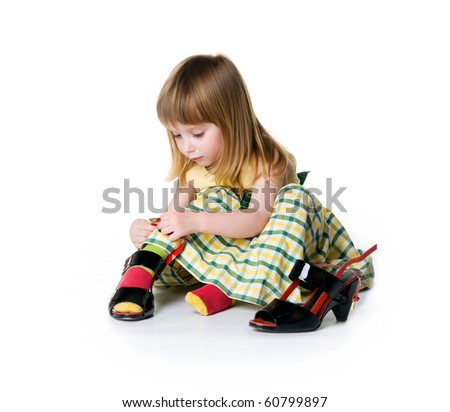 Little girl try on big shoes. Isolated on white background - stock photo