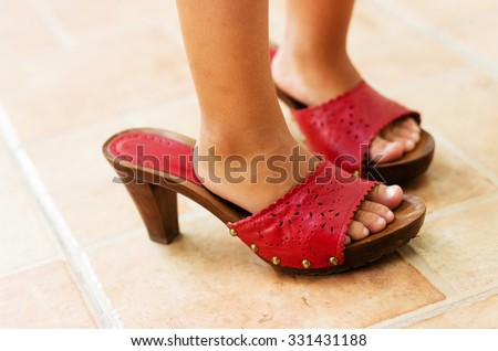Little girl trying her mother's red shoes  - stock photo