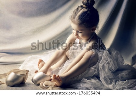 Little girl trying on ballet shoes - stock photo
