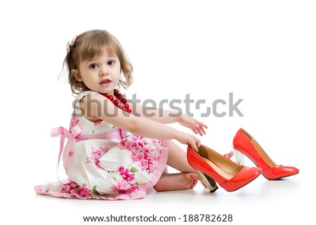 Little girl trying on mummy's shoes - stock photo