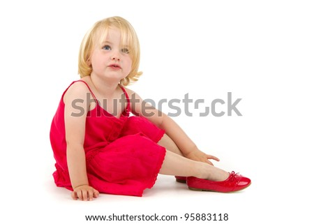 little girl trying on the big shoes on white background - stock photo