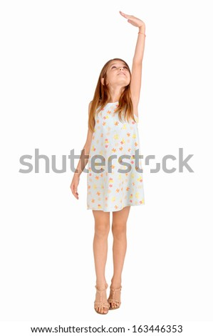 little girl trying to be taller isolated in white