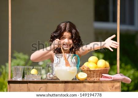 little girl trying to sell lemonade - stock photo