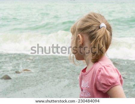 Little girl turning back to look at storming sea - stock photo