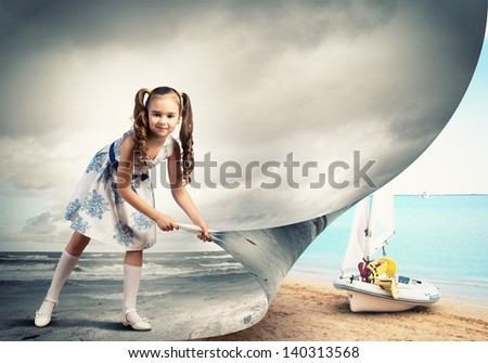Little girl turning page with another reality - stock photo