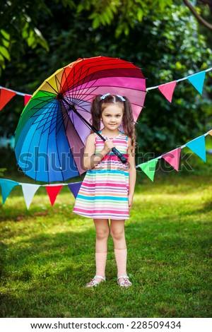 Little girl under rainbow colored umbrella - stock photo