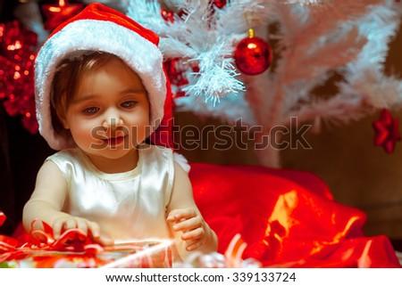 little girl unpacks the gift under the Christmas tree. Christmas mood. New year. - stock photo