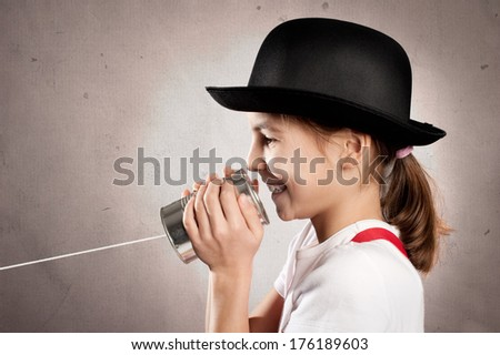 little girl using a can as telephone on a gray background